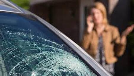 broken windshield with a woman on her on the background